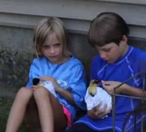 two kids holding ducks