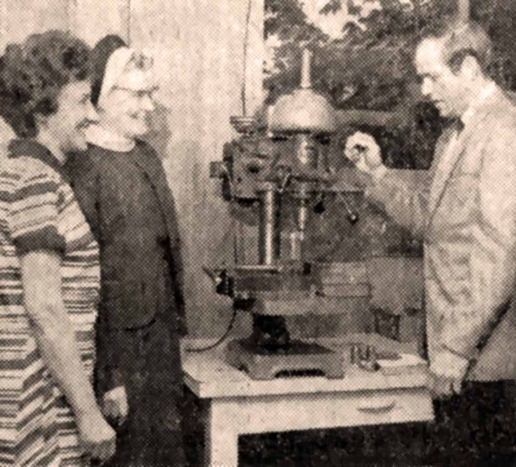 old photo of people using a machine