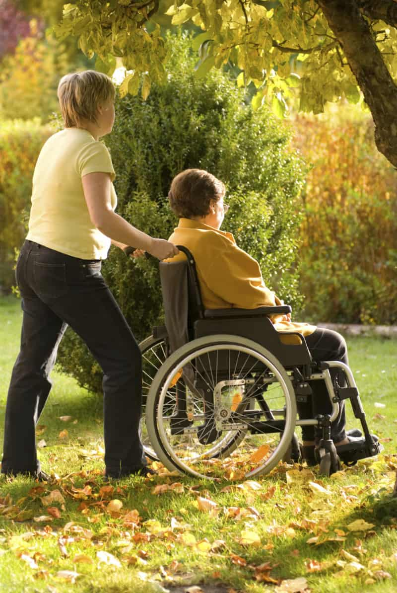 a woman pushing another woman in a wheelchair