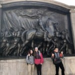 kids standing in front of a statue