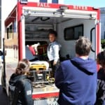 EMT workers showing a young boy the back of an ambulance