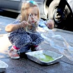 a young girl blowing bubbles on the sidewalk