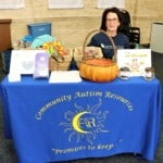 a woman sitting at a Community Autism Resources booth