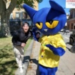 a man with a large blue mascot cat