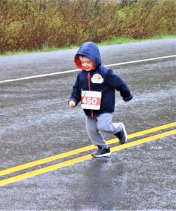a young boy running in the rain
