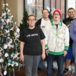 a people standing next to a Christmas tree