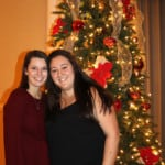 two women smiling in front of a Christman tree