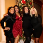 four women smiling in front of a Christman tree