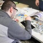 man building with Legos