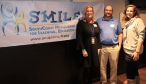 three people standing in front of a SMILES banner