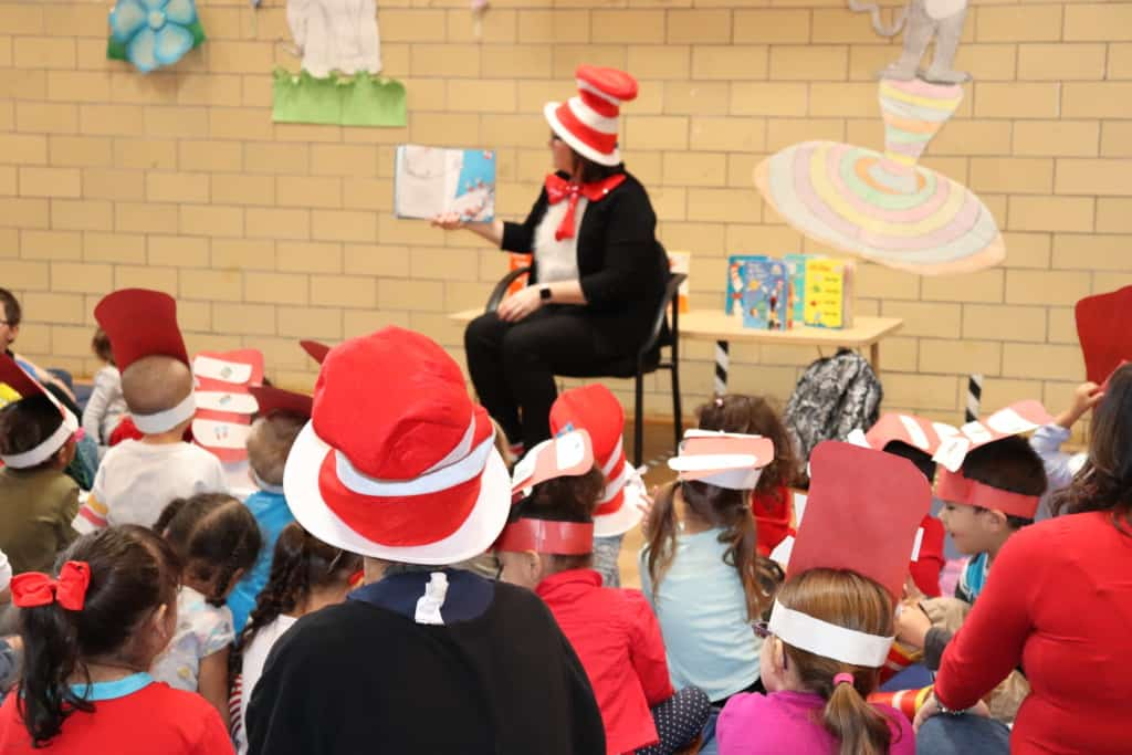 kids listening to a women who is dressed up in a red and white hat