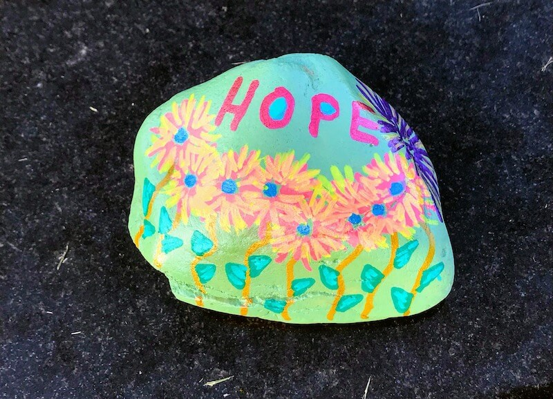"a rock with colorful paint on it and the word ""HOPE"" in paint"
